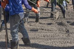 Arbeiders die een houten spatel voor cement na het Gieten van ready-mixed beton gebruiken royalty-vrije stock foto's