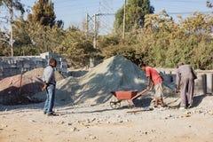 Arbeiders die een kruiwagen met zand laden Stock Afbeeldingen