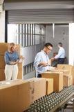 Arbeiders die Goederen controleren op Riem in Distributiepakhuis Stock Foto's