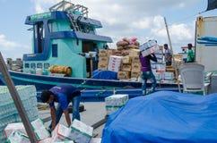 Arbeiders die goederen in leveringsboot laden Stock Foto's