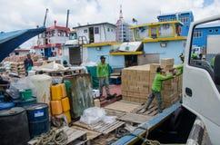 Arbeiders die goederen in leveringsboot laden Stock Afbeelding