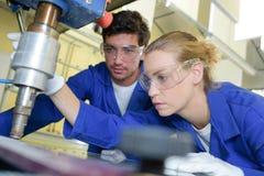 Arbeiders die industriële machine met behulp van royalty-vrije stock afbeelding