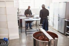Arbeiders die ingrediënten in een chocoladebereidingsfabriek voorbereiden stock afbeeldingen
