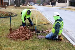 Arbeiders die lek op watermeter bevestigen en zeer natte modder op koude dag in Tulsa Oklahoma de V.S. 2 22 2018 uitgraven stock foto