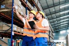 Arbeiders die in logistiekpakhuis bij vorkheftruck lijst controleren stock fotografie