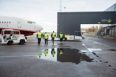 Arbeiders die naar Vliegtuig op Natte Baan lopen stock foto