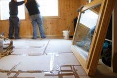 Arbeiders die nieuwe vensters installeren stock fotografie