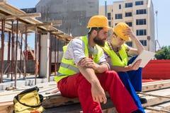 Arbeiders die of op een video op een tabletpc lezen letten tijdens onderbreking op het werk stock fotografie
