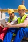 Arbeiders die of op een video op een tabletpc lezen letten tijdens onderbreking op het werk stock foto