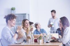 Arbeiders die op het kantoor eten royalty-vrije stock foto's
