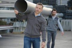 2 arbeiders die pijp dragen bij fabriekspakhuis royalty-vrije stock afbeeldingen
