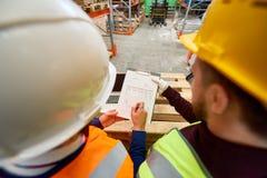 Arbeiders die Plannen bekijken stock foto's