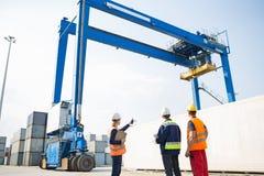 Arbeiders die tegen de grote container van de kraanlading bij het verschepen van werf bespreken Stock Afbeeldingen