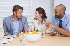 Arbeiders die terwijl het genieten van van gezonde lunch babbelen royalty-vrije stock afbeeldingen