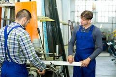 Arbeiders die vensterprofielen snijden Royalty-vrije Stock Fotografie