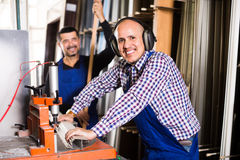 Arbeiders die vensterprofielen snijden stock foto's