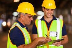 Arbeiders die voorraad controleren stock foto