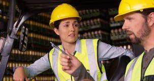 Arbeiders die in vorkheftruck zitten en aan elkaar in pakhuis spreken stock video