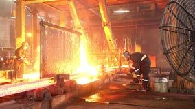 Arbeiders die vurige staalblokken snijden stock footage