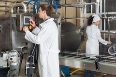 Arbeiders die zuivelproductieproces tonen Stock Foto's