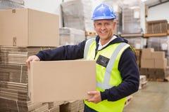 Arbeiders dragende doos in pakhuis Stock Foto's