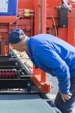Arbeiders dringende knopen op CNC de raad van de machinecontrole in fabriek De arbeiderswerken bij een houtbewerkingsonderneming  stock foto