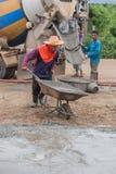Arbeiders duwende kruiwagen met nat cement aan het gieten van concrete vloer Stock Afbeeldingen