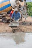 Arbeiders duwende kruiwagen met nat cement aan het gieten van concrete vloer Stock Afbeelding