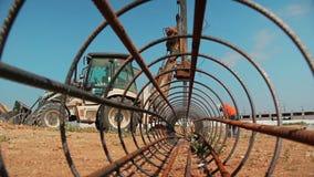 Arbeiders en een tractor met een boorapparaat bij een bouwwerf - bekijk van binnenuit de staaf van het bouwstaal stock video