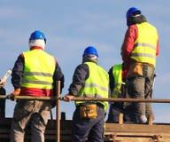 Arbeiders in gele en blauwhelm op de bouwwerf stock afbeeldingen
