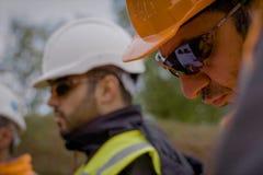 Arbeiders in helmen op de bouwwerf Bouwwerkzaamheden royalty-vrije stock foto