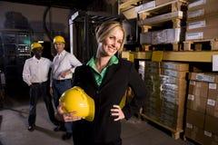 Arbeiders met vrouwelijke werkgever in opslagpakhuis Stock Foto's