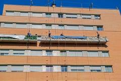 Arbeiders op de buitensteigerlift om het gebouw te herstellen Stock Afbeeldingen