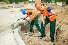 Arbeiders op een wegenbouw Stock Foto's