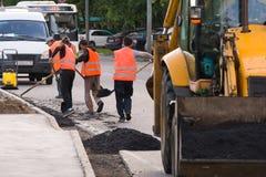Arbeiders in overall gelegd asfalt langs de rand op de rijweg stock foto's
