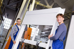 Arbeiders in overtrek met pvc-venster met blind stock foto
