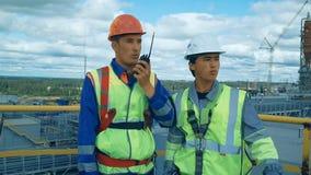 Arbeiders in productie-installatie als team die, industriële scène op achtergrond bespreken stock videobeelden