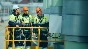 Arbeiders in productie-installatie als team die, industriële scène op achtergrond bespreken stock video