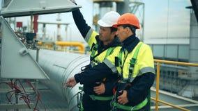 Arbeiders in productie-installatie als team die, industriële scène op achtergrond bespreken stock footage