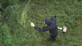 Arbeiders scherp gras, die de snoeischaar van het benzinegazon in de zomertuin met behulp van Gezoem binnen stock videobeelden