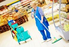 Arbeiders schoonmakende vloer met zwabber stock afbeelding