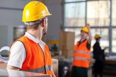 Arbeiders tijdens baan in fabriek Stock Foto