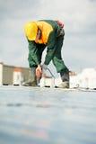 Arbeidersbouwer roofer aan het werk van het metaalprofiel stock afbeeldingen