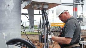 Arbeiderscontroles voorbereide kabels tegen transformatorhulpkantoor stock videobeelden