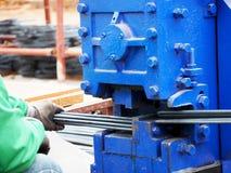 Arbeidershanden die staaldraad snijden stock foto's