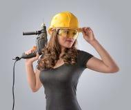 Arbeidersmeisje in een helm met een boor Royalty-vrije Stock Afbeeldingen