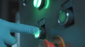 Arbeidersvinger in rubberhandschoendrukknop op metaalcontrolebord stock video