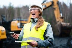 Arbeidersvrouw in bovengrondse mijnbouw die telefoon met behulp van stock foto
