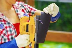Arbeidersvrouw die het schuurpapier verwijderen uit de elektrische schuurmachine royalty-vrije stock afbeeldingen