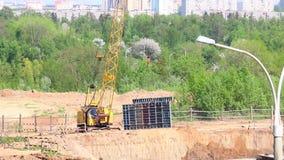 Arbeit über die Baustelle Der Baukran bewegt die Gebäudestrukturen stock footage